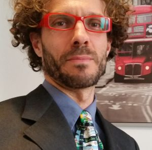 foto di stefano roganti in giacca e cravatta con occhiali rossi e cravatta multicolor irlandese