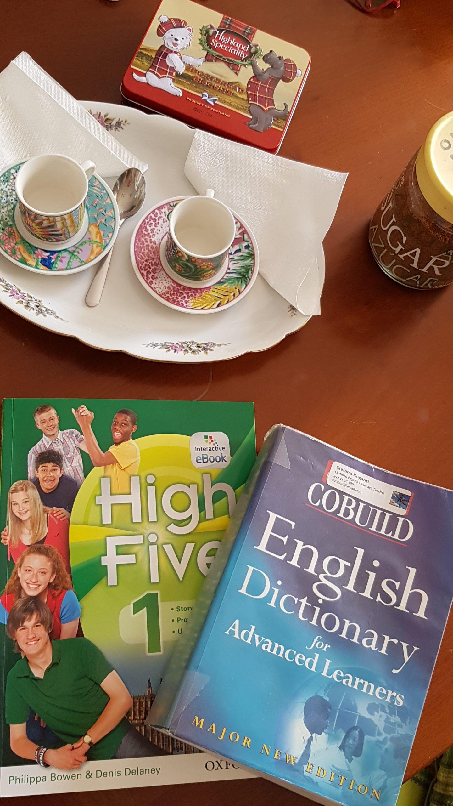 tavolo imbandito con libri, dizionari e tè